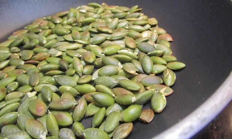 Pepitas roasting in a pan.
