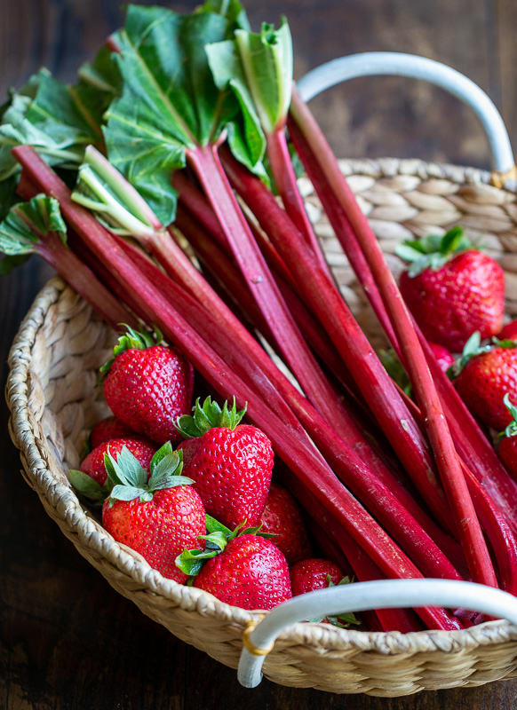 In a woven basket fresh rhubarb stalks and fresh whole strawberries.