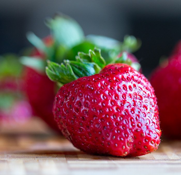 Whole fresh strawberry just washed with drips of water glistening on a bamboo cutting board.