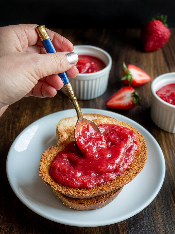 Strawberry rhubarb refrigerator jam getting spooned over 2 slices of toast.