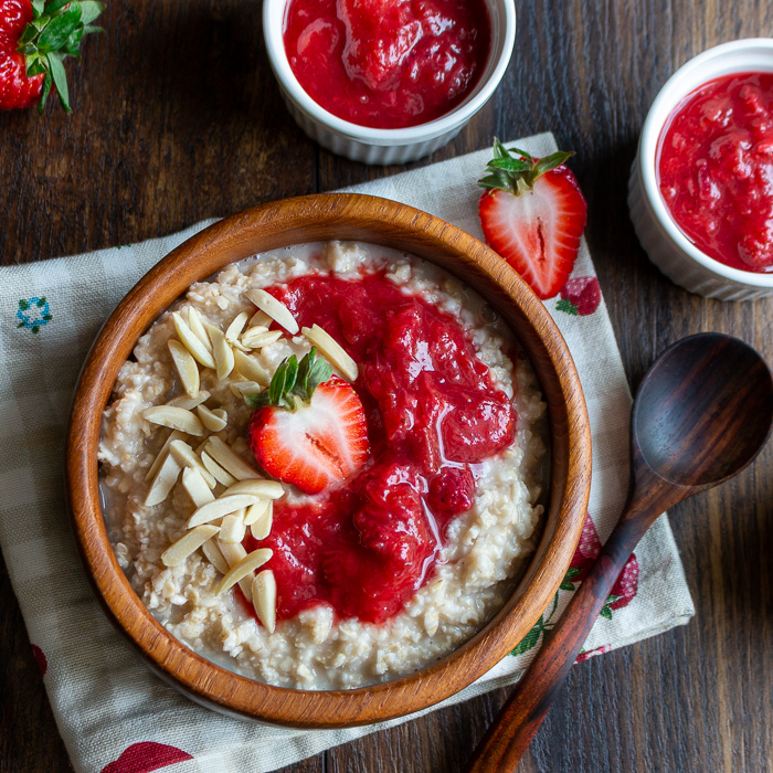 Bowl of oatmeal garnished with strawberry rhubarb jam, almonds and fresh strawberries in a wooden bowl.