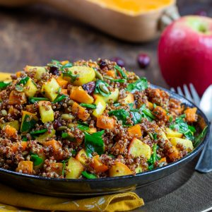 Quinoa Harvest Salad in a black bowl with apples and butternut squash in the background.