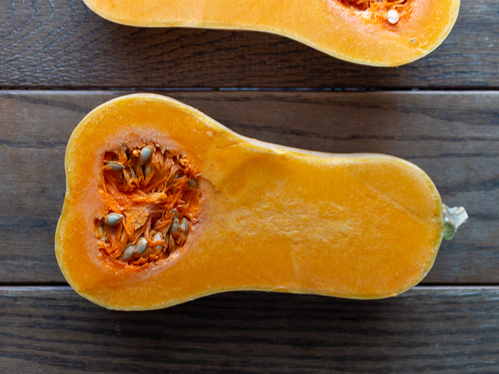 butternut squash cut in half showing its seeds on a wooden table.