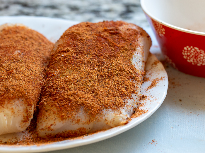 Cod fish seasoned with cajun seasoning ready to be pan fried.