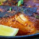 Close up shot of flaky cajun cod with a wedge of lemon.