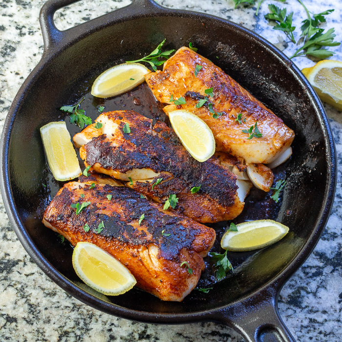 3 fish fillets in an iron skillet garnished with lemons and herbs.
