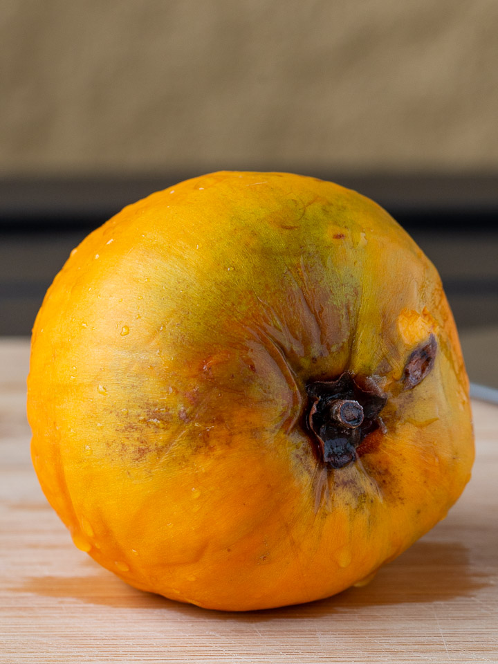 Whole bright yellow orange canistel sitting on a cutting board.