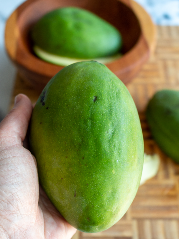 Bright green mango held in a hand.