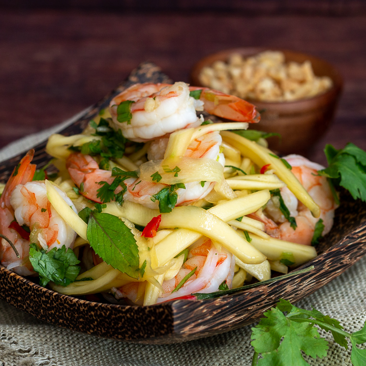 Thai Shrimp Green Mango Salad on a wooden plate.