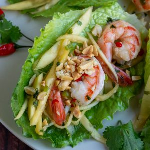 Thai Shrimp mango salad in a lettuce cup garnished with crushed peanuts.