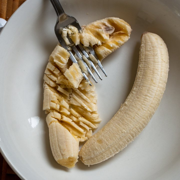 Two ripe bananas getting mashed with a fork in a white bowl.