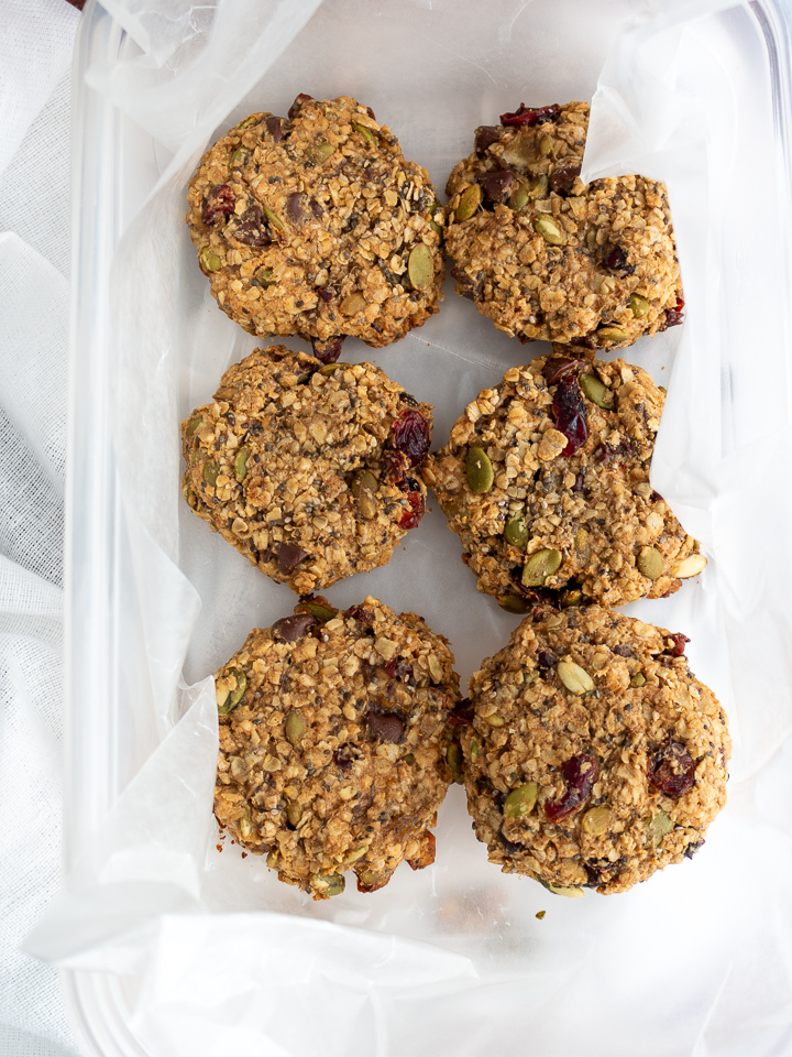 Showing baked and cooled cranberry Oatmeal Breakfast cookies in a freezer safe sealed container lined with layers of parchment paper between each to prevent sticking.