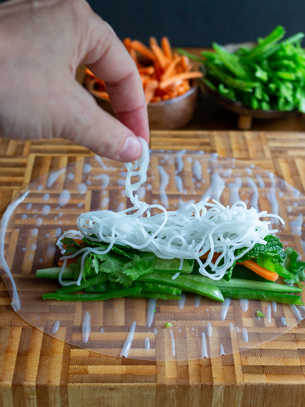 Adding rice vermicelli noodles on top of vegetables and fresh herbs.