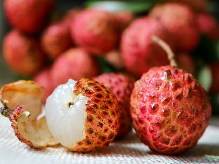 Fresh lychees with one peeled showing the white flesh.