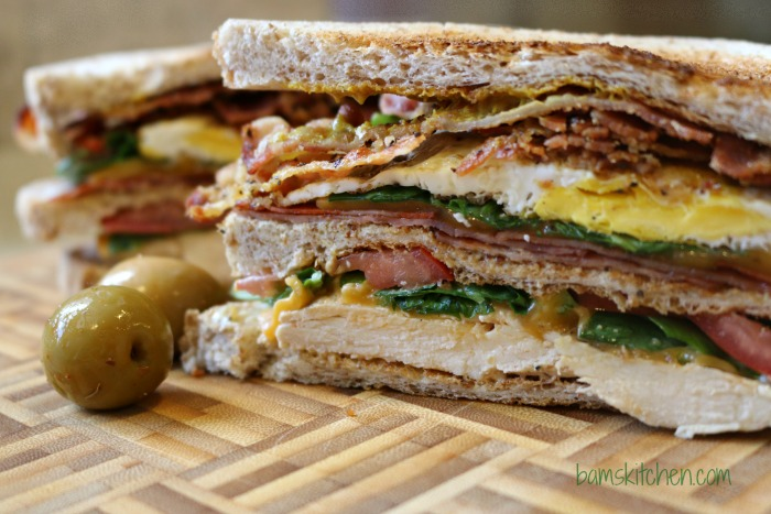 Triple Decker Sammie cut in half showing all the layers and additions with a couple of olives on the side.