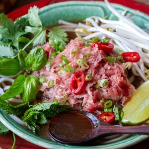 Quick beef pho in a green bowl with a spoonful of soup and lots of fresh herbs.