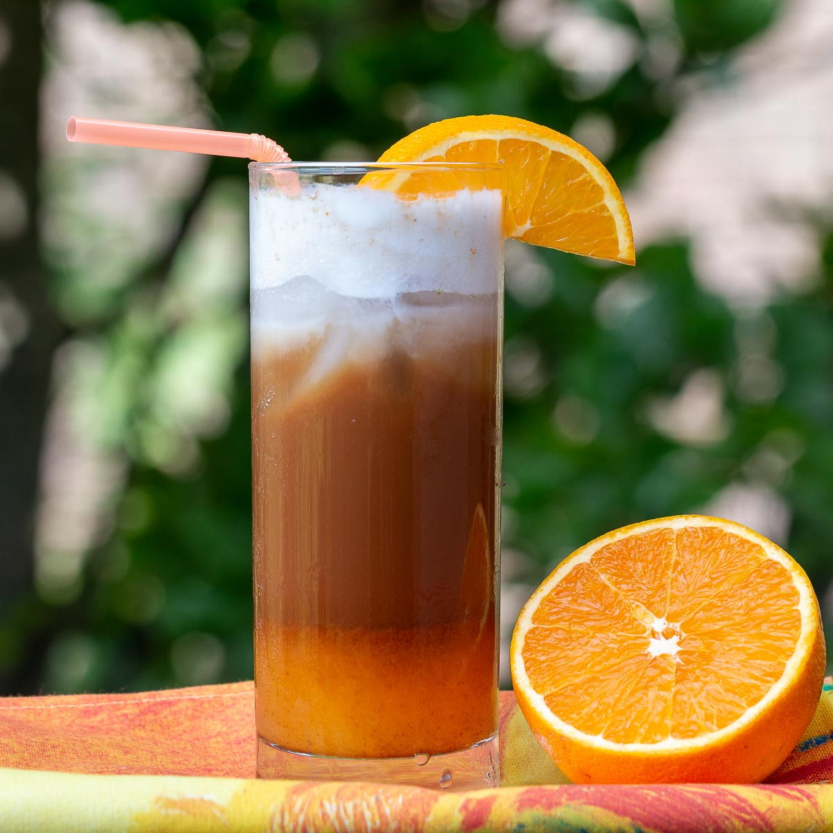 Outside sunny shot of iced bumblebee coffee garnished with oranges.