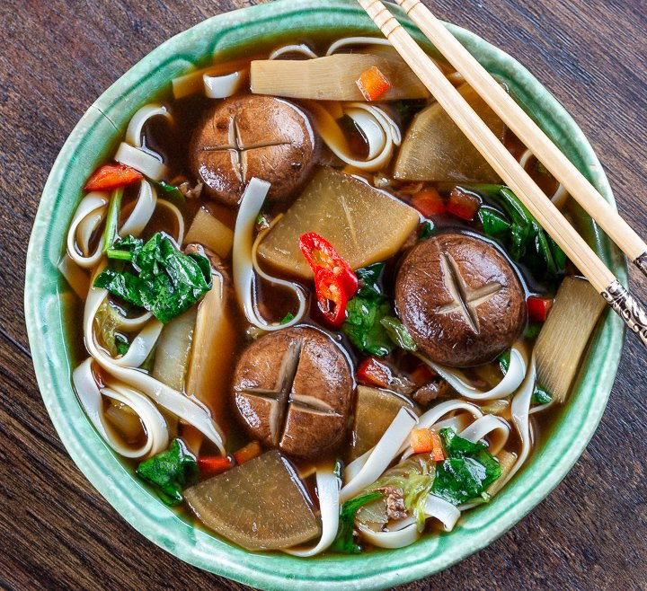 Delicious top down photo of Chinese Beef Noodle Soup Recipe in a green bowl with chopsticks.