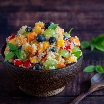 Quinoa fruit salad in a wooden bowl garnished in mint with a wooden spoon.