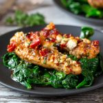 2 delicious Feta Baked chicken tenderloins over a bed of sautéed garlicky spinach on a black plate.