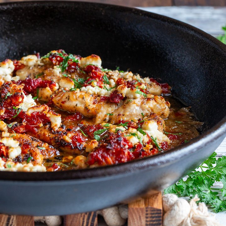 Close up of a cast iron skillet with the baked feta chicken inside.