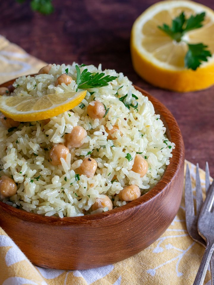 Easy rice pilaf and garbanzo beans in a wooden bowls garnished with lemons and parsley.