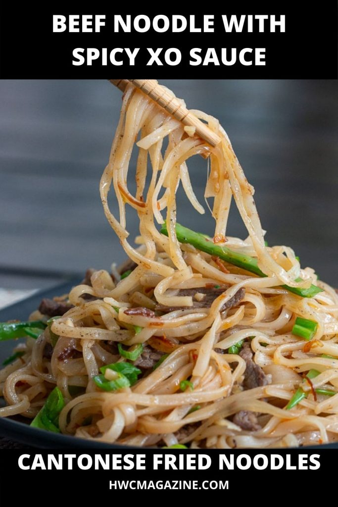 Pan fried Cantonese beef noodles with spicy XO sauce picked up with chopsticks.