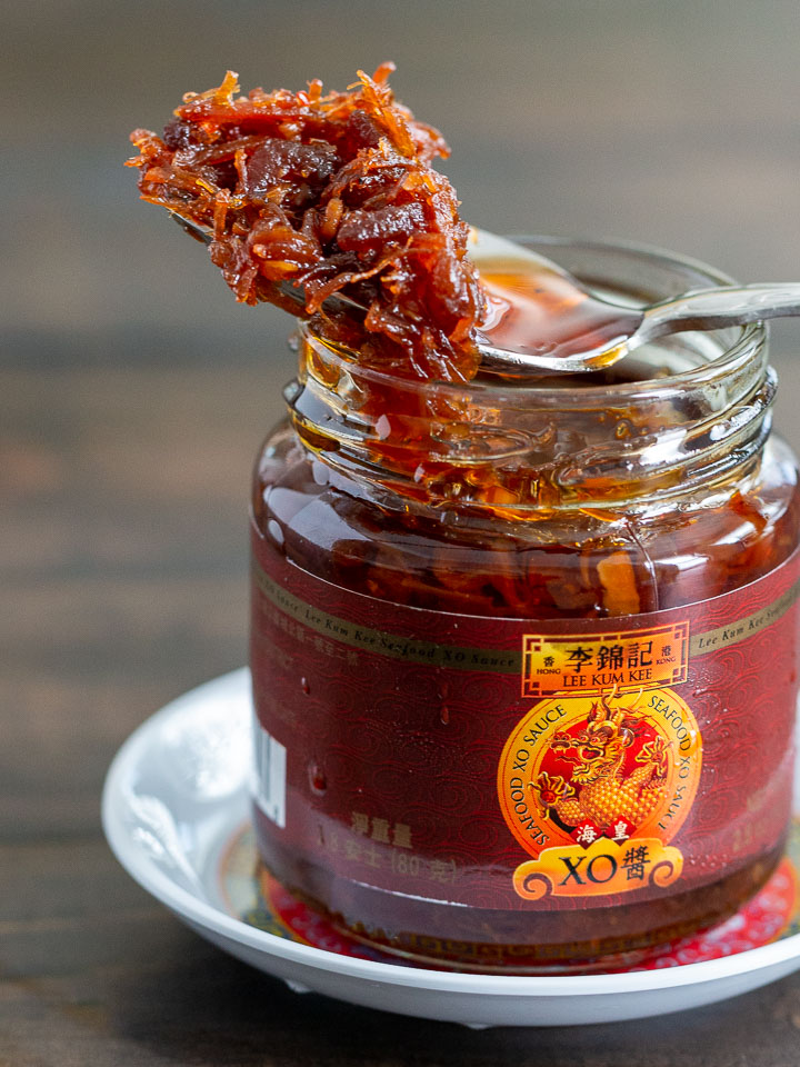 Big spoonful of XO sauce sitting on the edge of a Lee Kum Kee container.