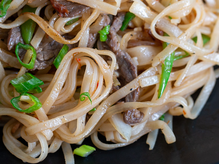 Close up shot of pan fried noodles perfectly cook and on a black dish.