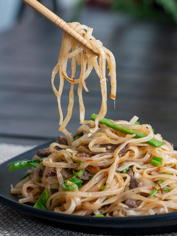 A spoonful of pan fried noodles picked up with chopsticks. Ready to eat.