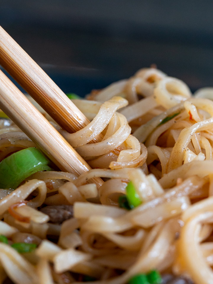 Noodles wrapped around chopsticks ready to eat.