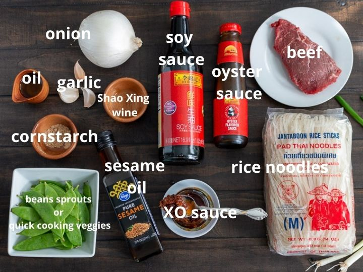 All ingredients to make Beef Noodles and spicy XO sauce laid out on a dark wooden board.