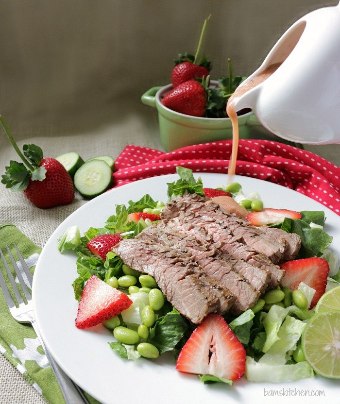 Strawberry cucumber salad dressing being drizzled over salad.