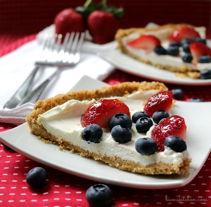 Mouthwatering slice of cheesecake bars with strawberries in the background.