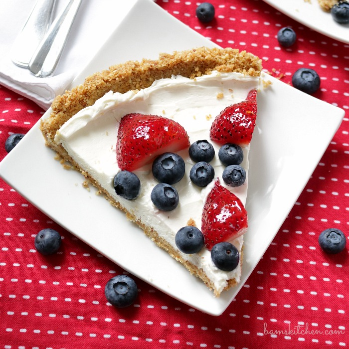 Slice of berry cheesecake on a white plate with a red and white napkin. Garnished with blueberries and strawberries.