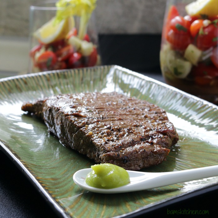 Grilled Steak right off the grill on a green plate.