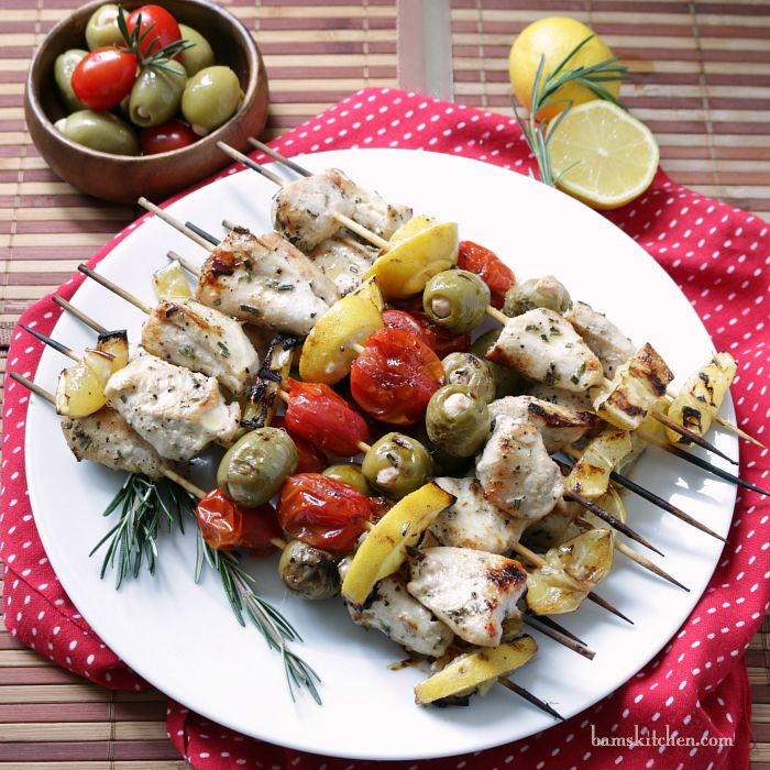 Mediterranean Chicken Kabobs on a white plate garnished with rosemary and lemons.