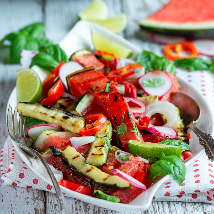 Thai Style Grilled watermelon salad on a white plate with a polka dot napkin.