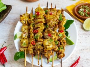 Thai pork Skewers perfectly grilled on a white plate next to a bowl of Thai basil dipping sauce.