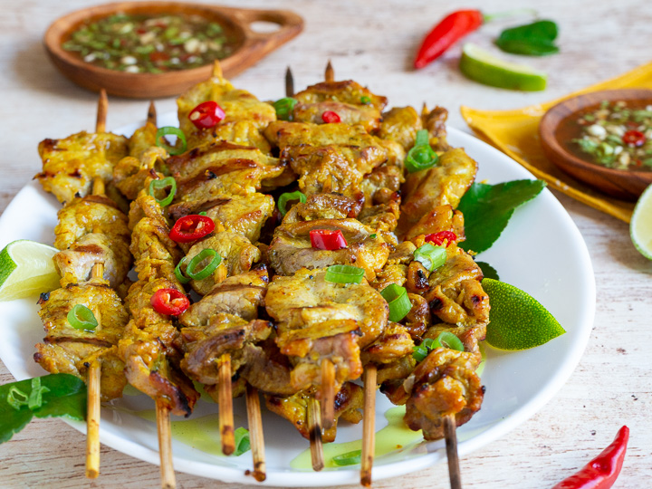 Perfectly tender grill pork tenderloins on skewers with prik nam pla sauce in wooden bowls.