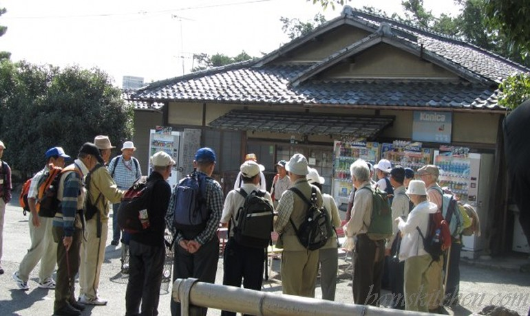 Group of Japanese males maybe in their 50-70's all wearing beige fishing vest and backpacks.
