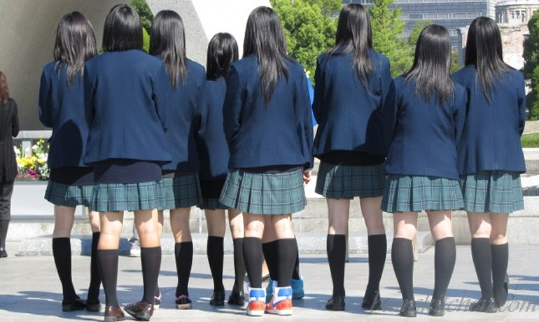 Japanese school girls all lined up with their backs to us and only one has a pair of high top tennis shoes on. LOL