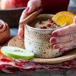 Hands wrapped around a cozy mug of hot apple cider.