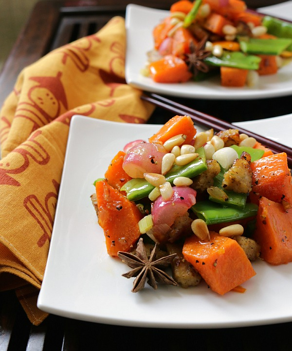 2 plates of delicious stir fried sweet potatoes and veggies topped with toasted pine nuts.