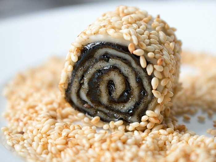 Cookie getting rolled in the sesame seeds ready to be baked.
