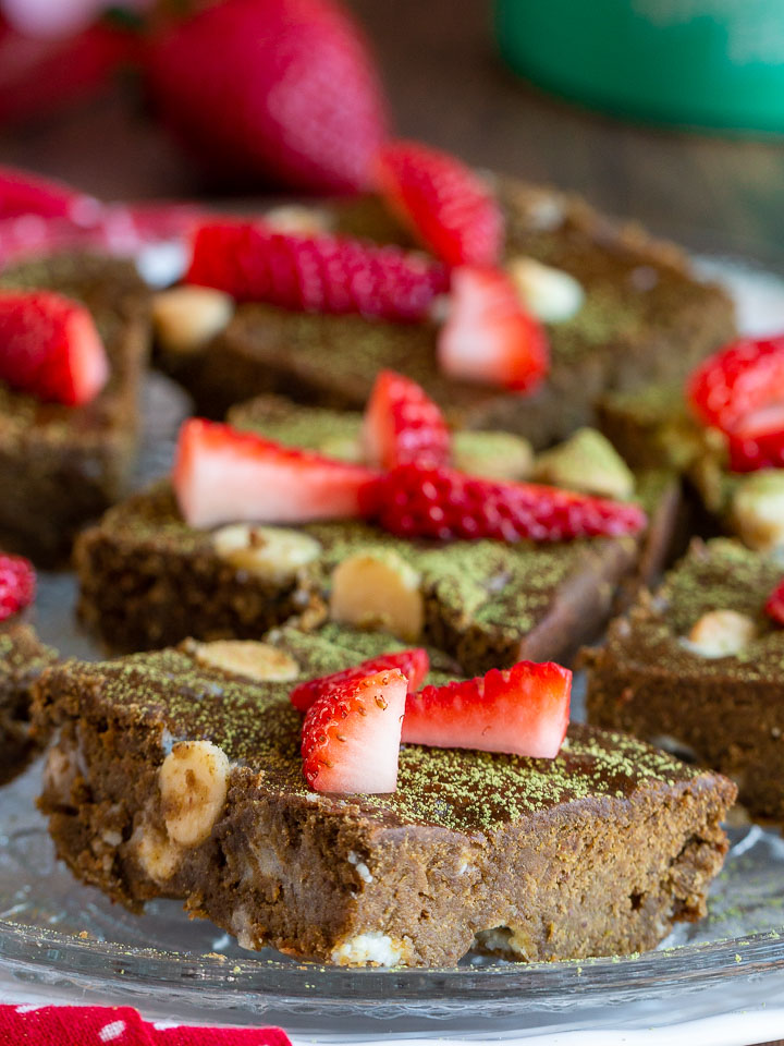 Many matcha brownies laid out on a white plate topped with strawberries.
