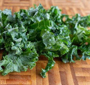 Kale on cutting board with stem vein removed and ready to chop.