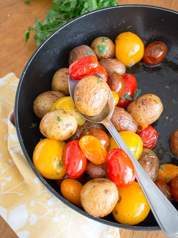 Potatoes and tomatoes in an iron skillet getting tossed in the brown butter.