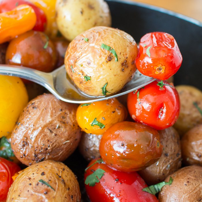 Potatoes and tomatoes on a spoon.