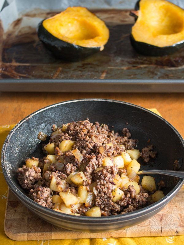 Double meat and apple mixture in an iron skillet with halves of cooked acorn squash in the background.